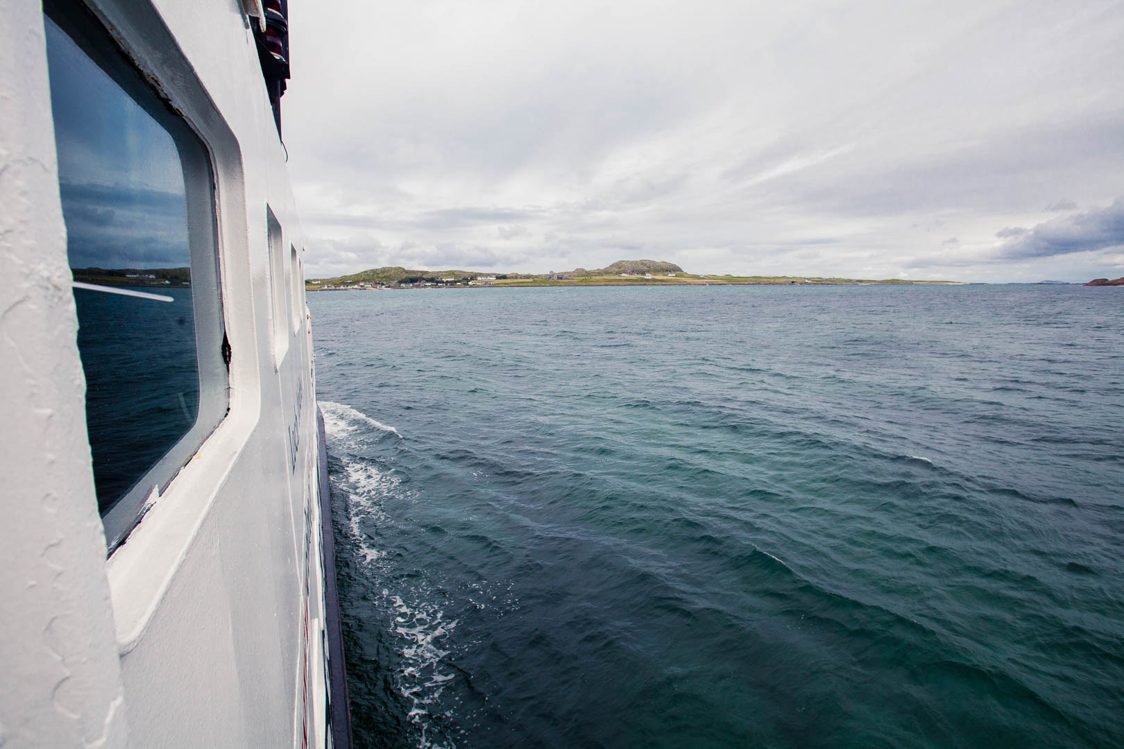 View from a boat at sea. The side of the boat is in the picture on the left and there is a green lat island in the distance on the horizon.