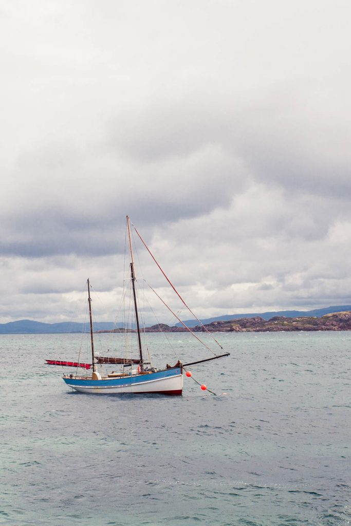 A blue and white sail boat with two masts anchored near the Isle of Iona.