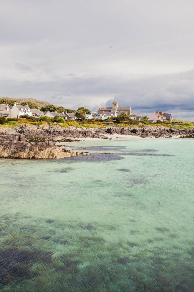 Image of the harbour of the Isle of Iona. The village and the medieval abbey are visible on land and the water is bright green as it is so clear and shallow.